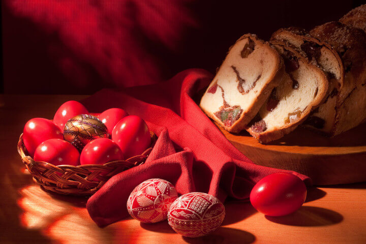 Red Romanian Easter Eggs on Table with Bread